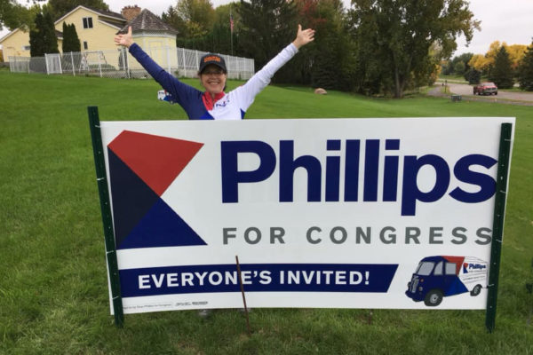Dean supporter standing with her Phillips for Congress yard sign